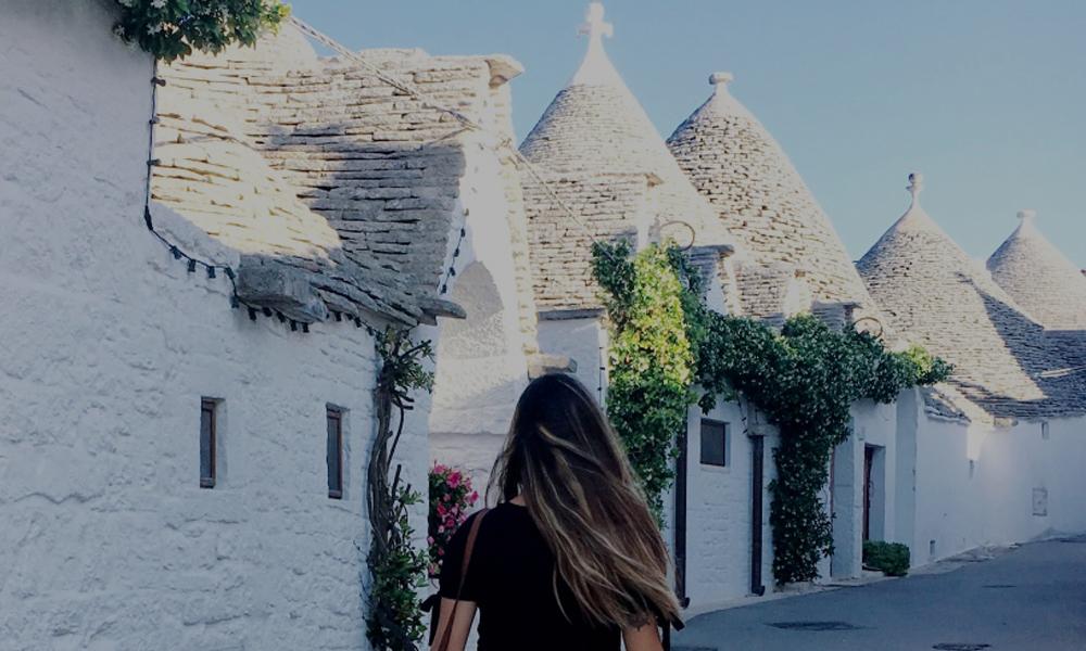 Una via del Rione Monti ad alberobello con trulli sullo sfondo e soggetto di spalle in primo piano