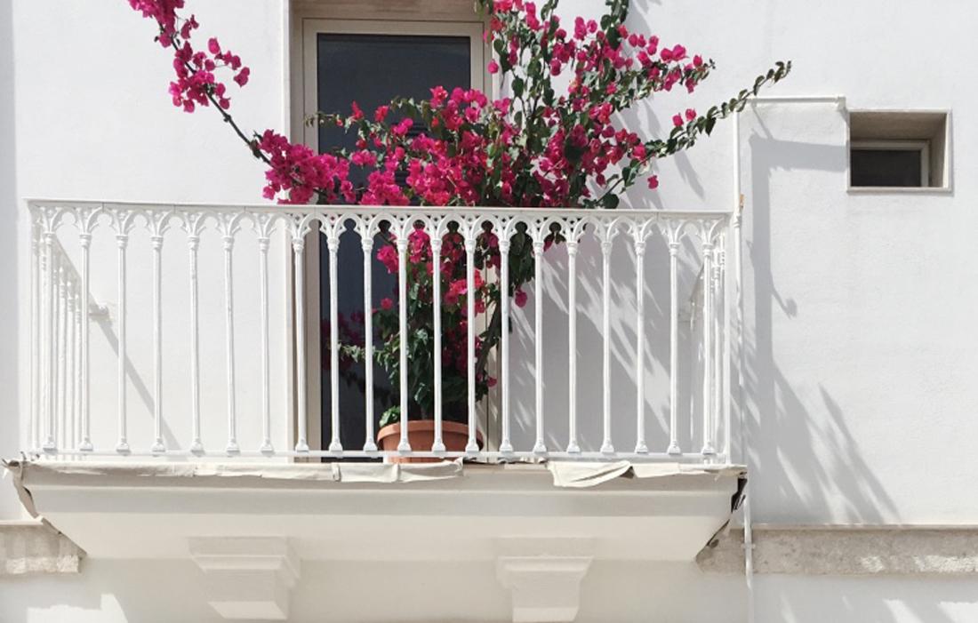Un caratteristico balconcino bianco ornato da fiori rosa fucsia a Polignano a Mare