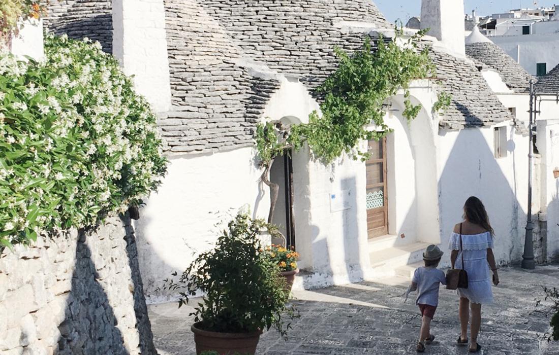 I trulli di Alberobello, Rione Monti, una donna e un bambino per mano di schiena