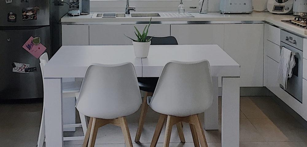 Una cucina in stile scandinavo con tavolo in legno bianco e sedie con zampe in legno chiaro. Sullo sfondo un frigo in acciaio e una grande finestra