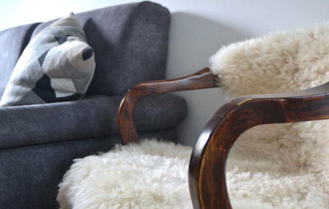 Divano grigio in stile nordico, cuscino con fantasia geometrica e poltrona in legno scuro con eco-pelliccia scandinava bianca
