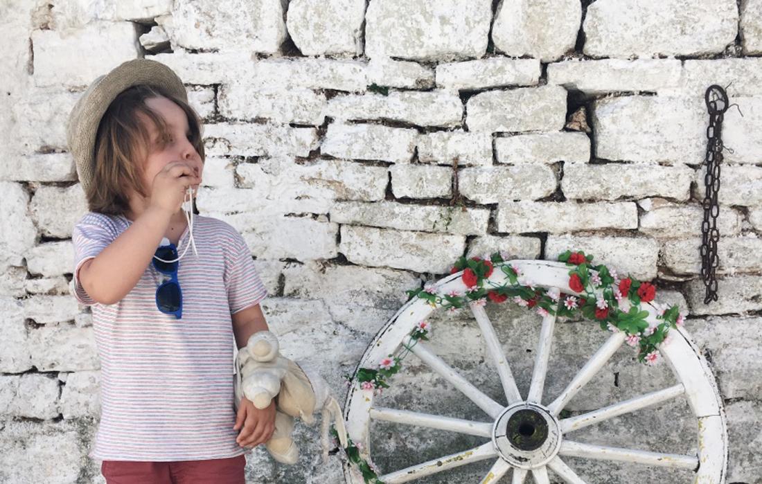 Un bambino intento a suonare il tipico fischietto in terracotta pugliese