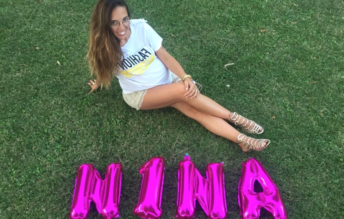 """Donna incinta al nono mese di gravidanza seduta su prato verde con gambe accavallate. In primo piano palloncini rosa fucsia con scritta """"Nina"""""""