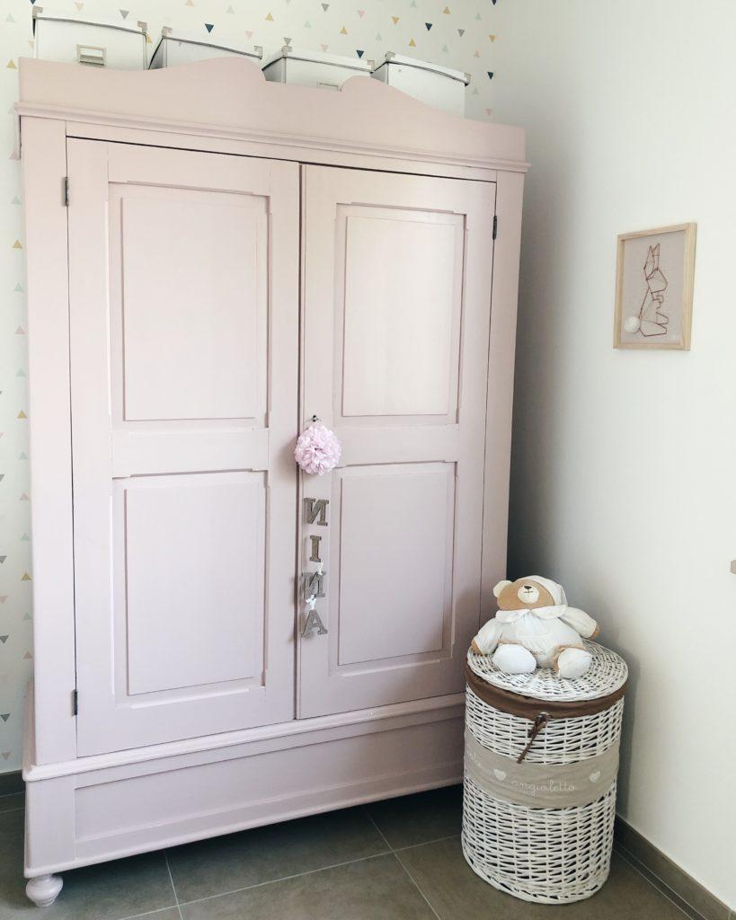 armadio antico riverniciato color rosa antico e decorazione con scritta appesa alla chiave. Di fianco, un peluche bianco a forma di orso. Appeso al muro, un quadretto con ritratto un coniglio in ferro e coda in peluche su cornice di legno chiaro.