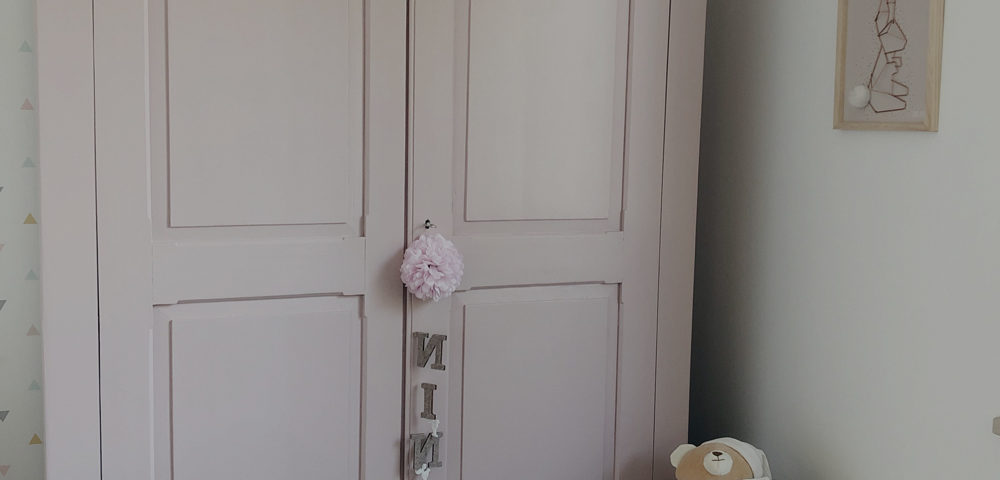 mobile antico riverniciato color rosa antico e decorazione con scritta appesa alla chiave. Di fianco, un peluche bianco a forma di orso. Appeso al muro, un quadretto con ritratto un coniglio in ferro e coda in peluche su cornice di legno chiaro.