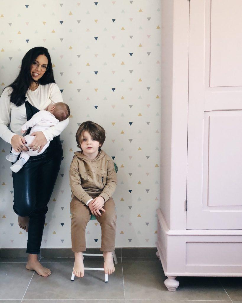 Carta da parati con triangoli colorati sullo sfondo, parte di mobile rosa antico e una mamma con in braccio una neonata. Seduto a fianco a lei un bambino di cinque anni.