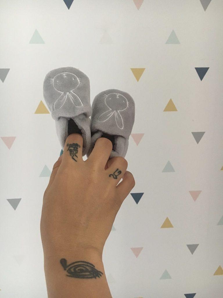 Carta da parati con triangolini colorati sullo sfondo e mano tatuata che sorregge due scarpette da neonato grigie