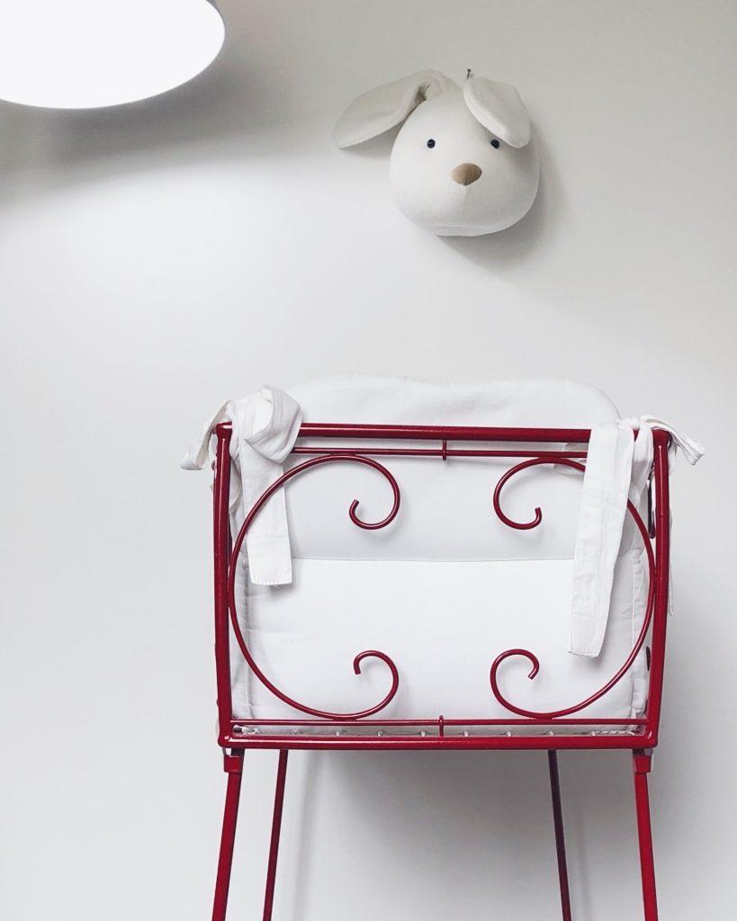 Culla in ferro battuto rossa con rivestimento bianco. Appesa al muro una decorazione a forma di testa di coniglio in stoffa. In alto a sinistra una lampada