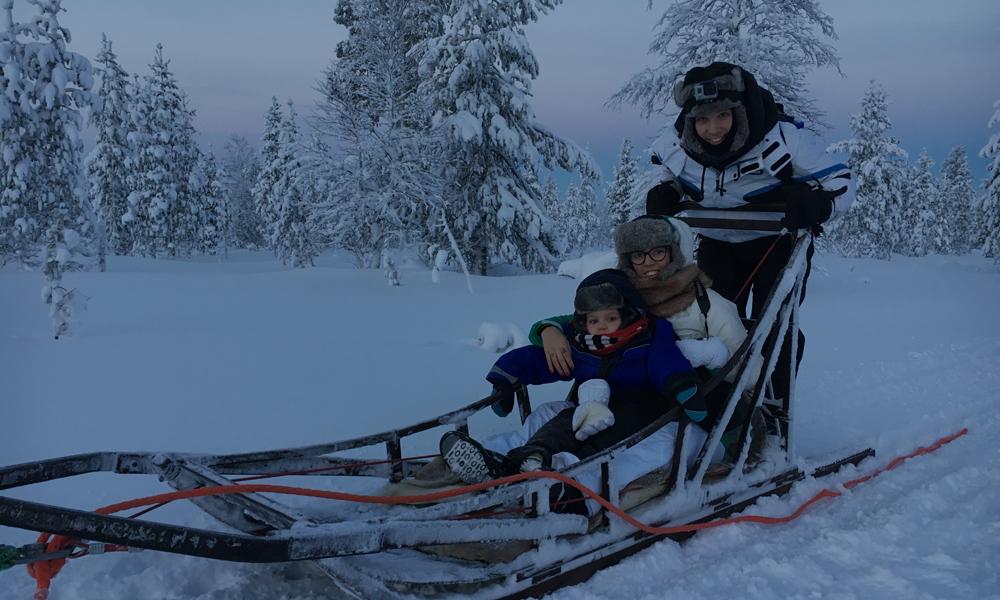 Un uomo, una donna e un bambino su una slitta trainata dagli husky. Sullo sfondo la foresta lappone.