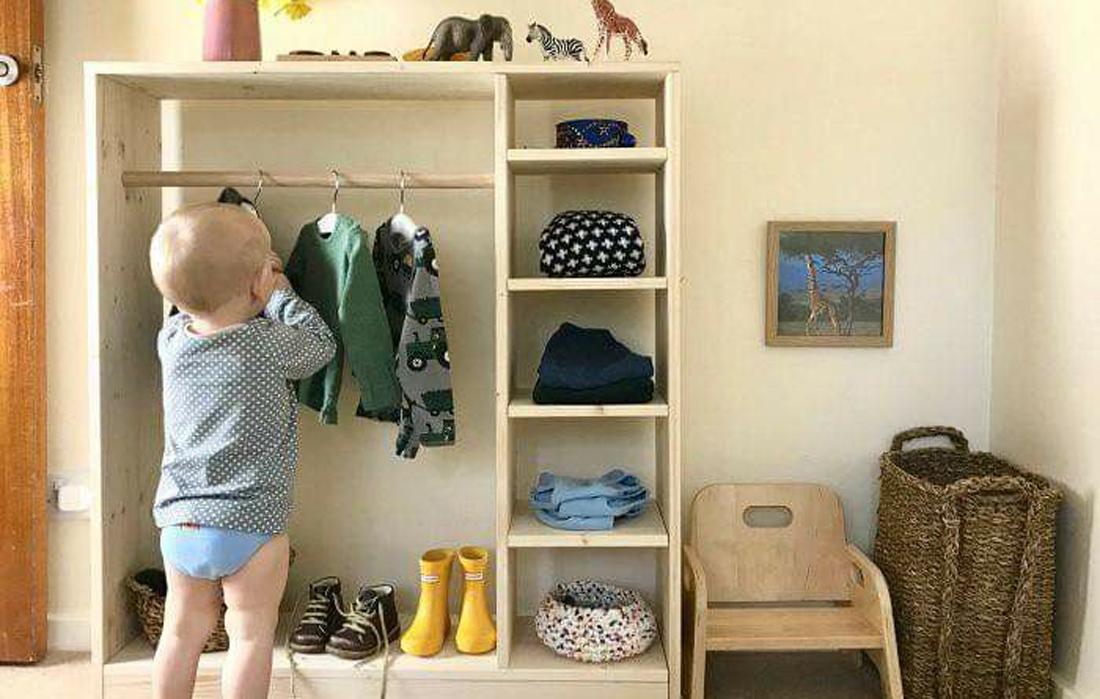 un bambino molto piccolo prende da solo i suoi vestiti nell'armadio posizionato alla sua altezza.