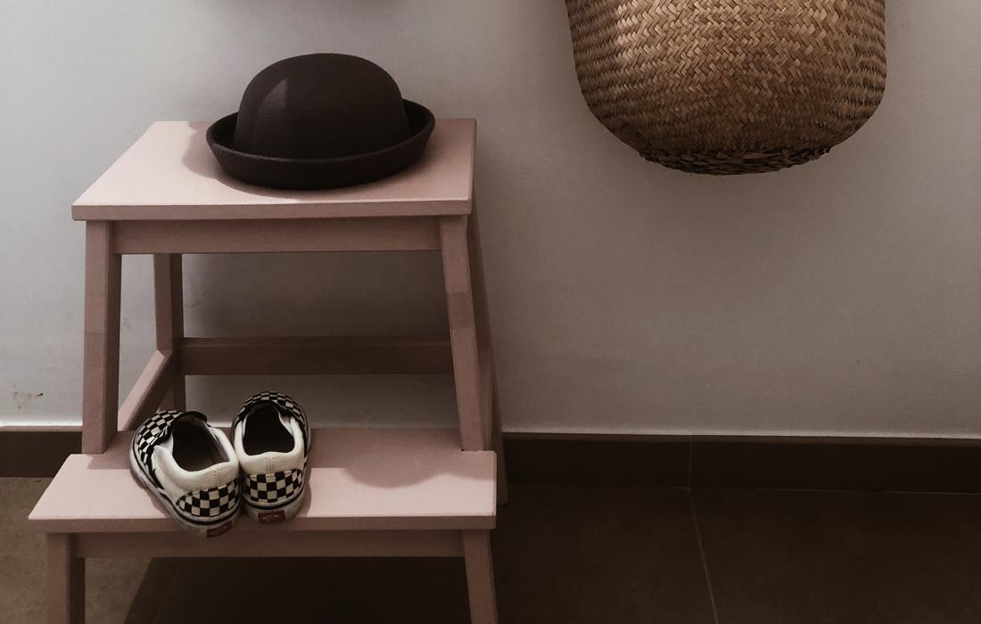 Sgabello basso per bambini con scarpe appoggiate sopra e un cappello. Di lato, una cesta in vimini per riporre cappelli, sciarpe e altri accessori.