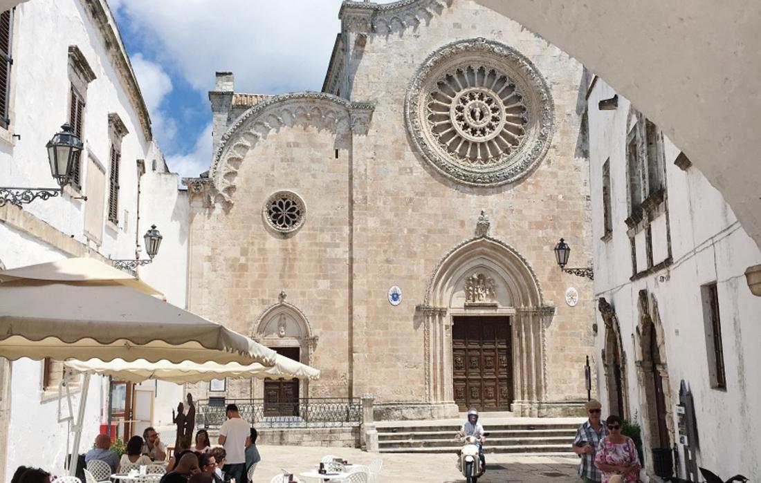 Il Duomo di Ostuni visto da dietro un'arco. Soggetto in vespa in lontananza