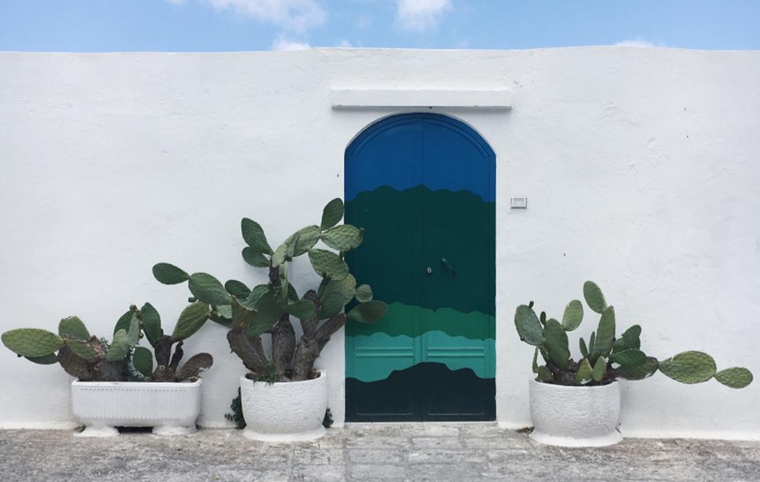 La porta azzurra di Ostuni, una porta pitturata sui toni dell'azzurro su una costruzione bianca. Ai lati, due cactus e sopra il cielo azzurro.
