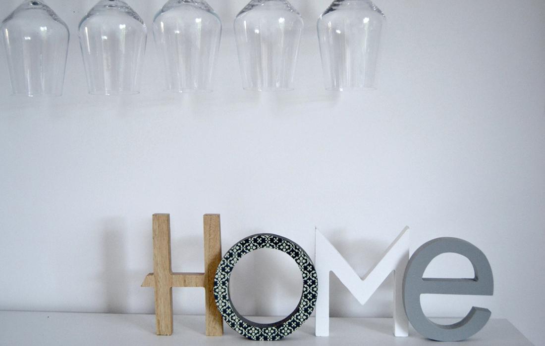 """Decorazione in legno con scritta """"home"""" e bicchieri da vino appesi"""