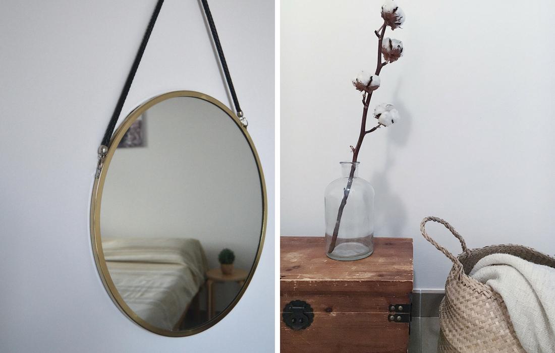 Dettagli di arredo scandinavo: uno specchio rotondo con cornice bronzo e una vecchia cassetta in legno con sopra un vaso con un fiore di cotone. Accanto una cesta di paglia dalla quale esce una coperta panna.