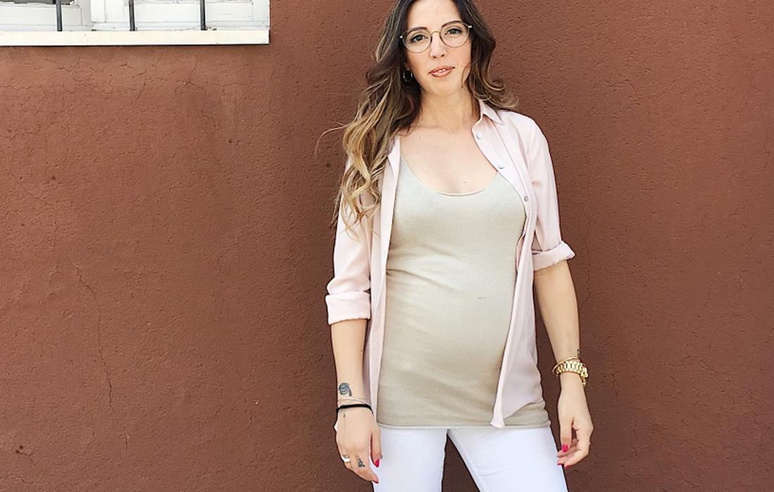 Donna incinta di 25 settimane, sullo sfondo un muro color mattone.