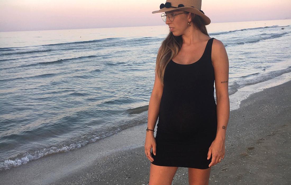 Donna incinta all'ottavo mese di gravidanza sulla riva del mare con abito corto nero e cappello in paglia, prospettiva frontale