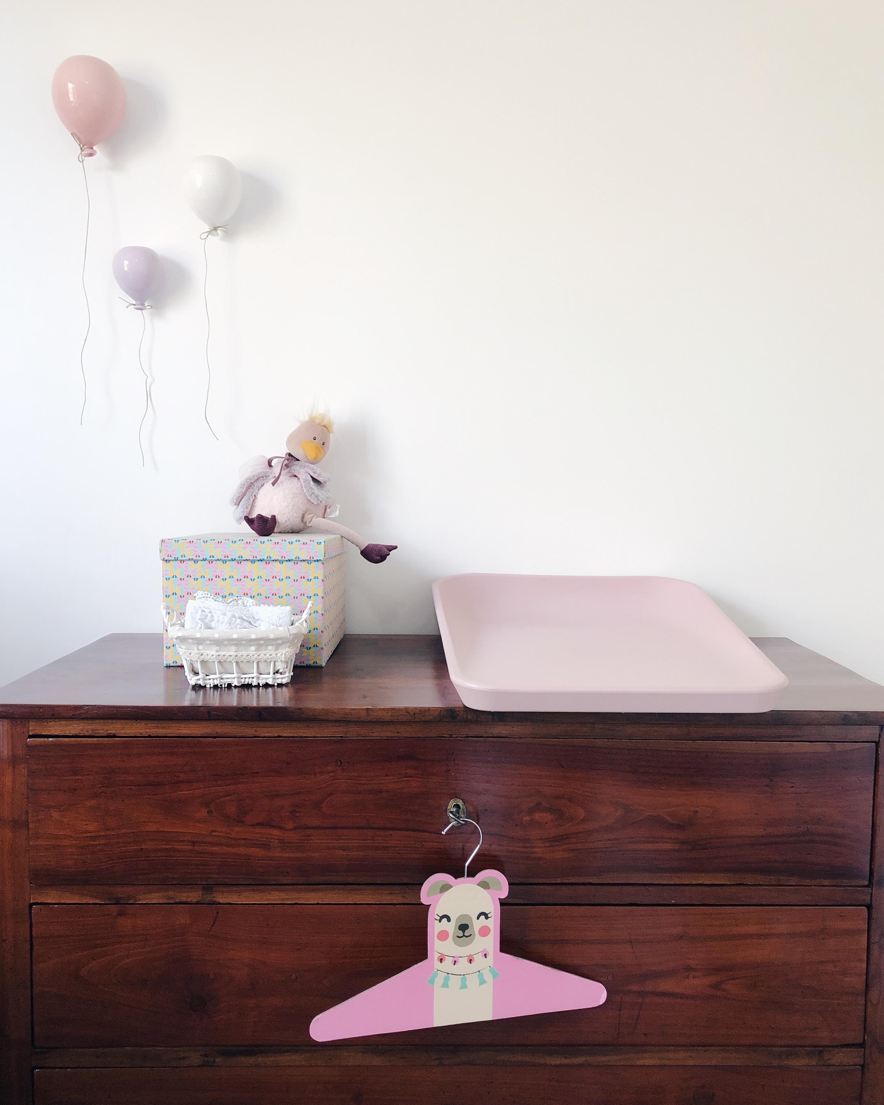 Cassettiera antica restaurata in legno scuro a tre cassetti con chiavi. Su una chiave è appeso un attaccapanni rosa con un orso disegnato. Sopra la cassettiera un cuscino fasciatoio rosa antico, una scatola colorata e un peluche rosa. Appese al muro tre decorazioni in ceramica a forma di palloncino