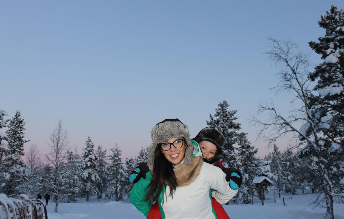 Mamma con figlio in spalle tra la neve