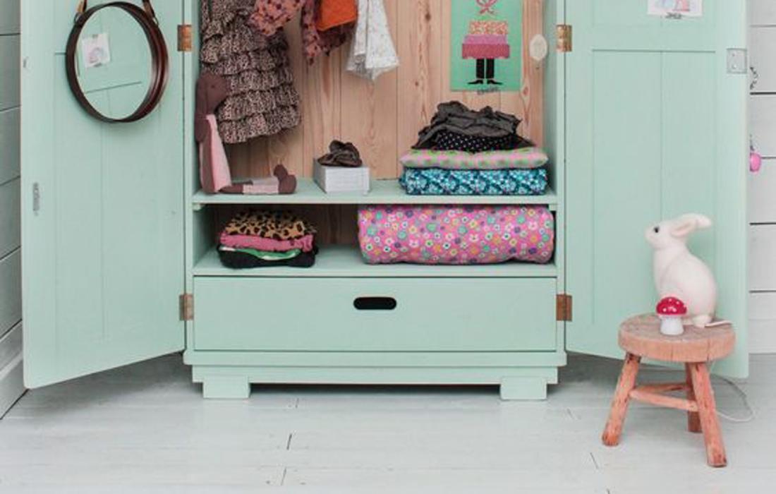 Armadio vintage in legno verniciato color verde pastello. All'interno alcuni indumenti riposti in modo ordinato