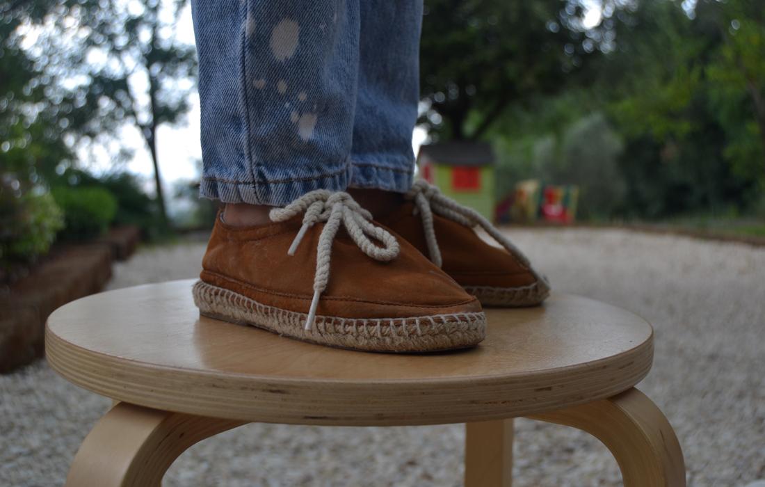 Piedi di bambino su uno sgabello di legno.