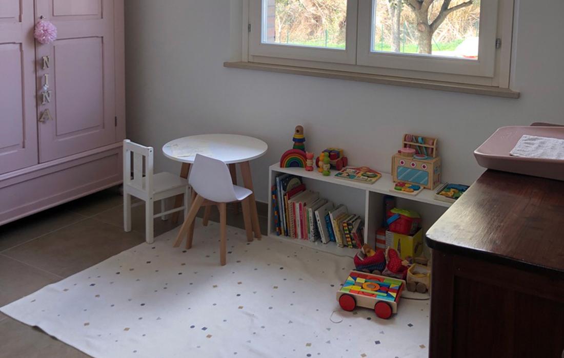 Cameretta da bambina con mobile basso, giochi in legno. Un tappeto a triangoli colorati e un tavolo basso rotondo bianco con gambe in legno naturale e due seggioline basse