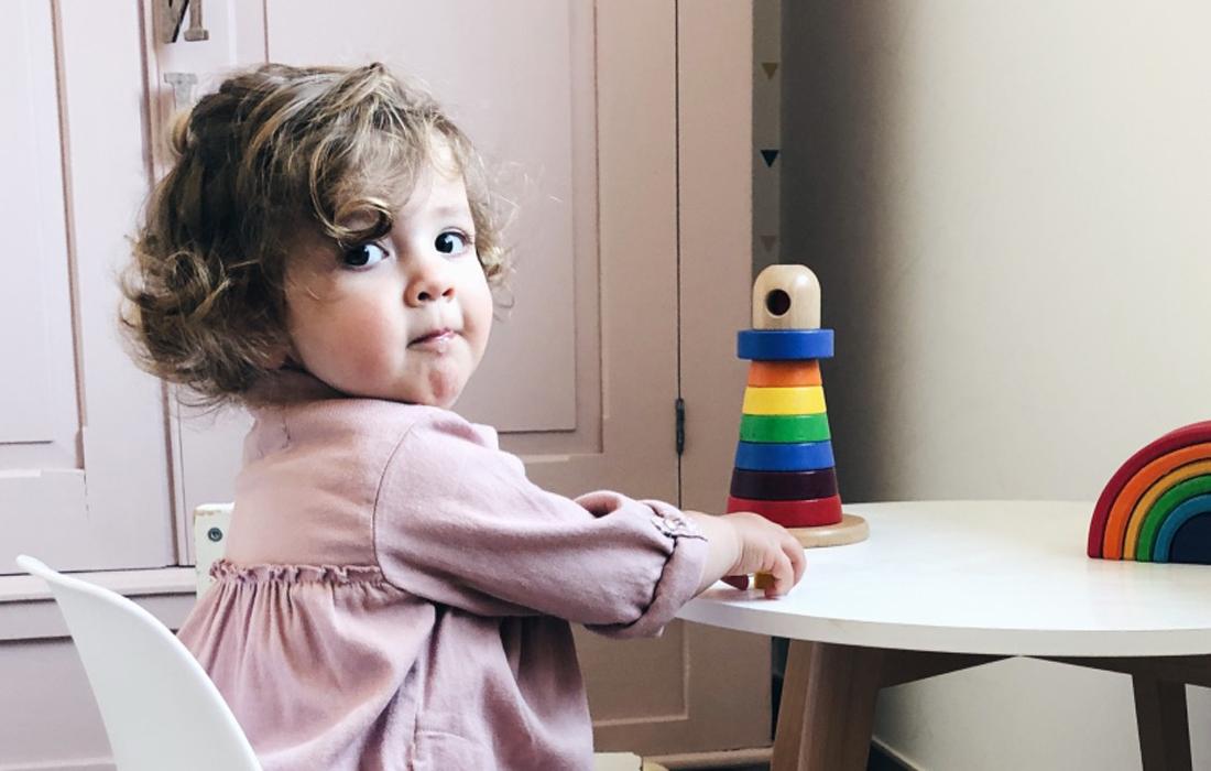 Bambina bionda vestita di rosa seduta su una seggiolina bianca. Di fronte un tavolinetto rotondo bianco sul quale sono posizionati due giochi il legno. Alle sue spalle, un armadio in legno color rosa.