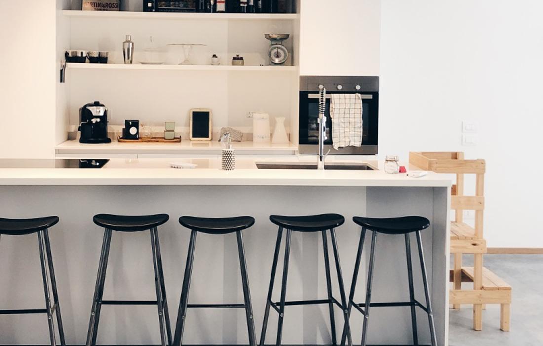 Cucina bianca con bancone e sgabelli neri. Di fianco una learning tower montessoriana in legno naturale.