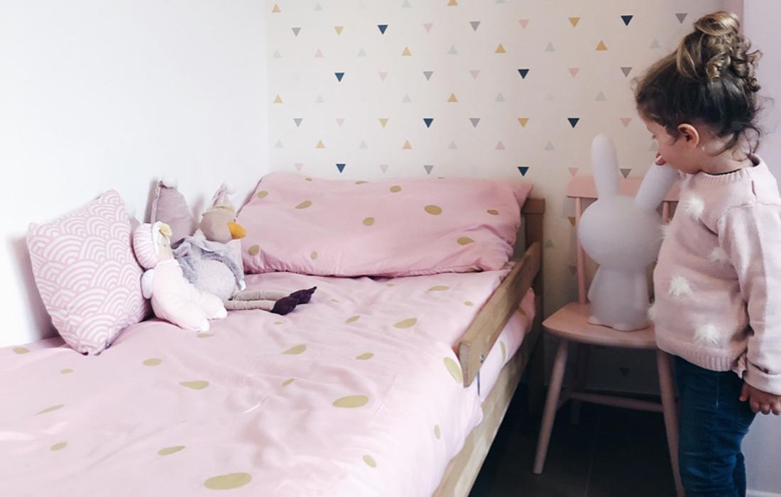 Lettino in legno basso da bambina con lenziola a pois rosa e oro. Sul letto dei peluches e di fianco una seggiolina rosa in legno sulla quale è appoggiata uno speacher bluetooth a forma di coniglio bianco. DI fronte una bambina con maglione rosa e jeans guarda il letto