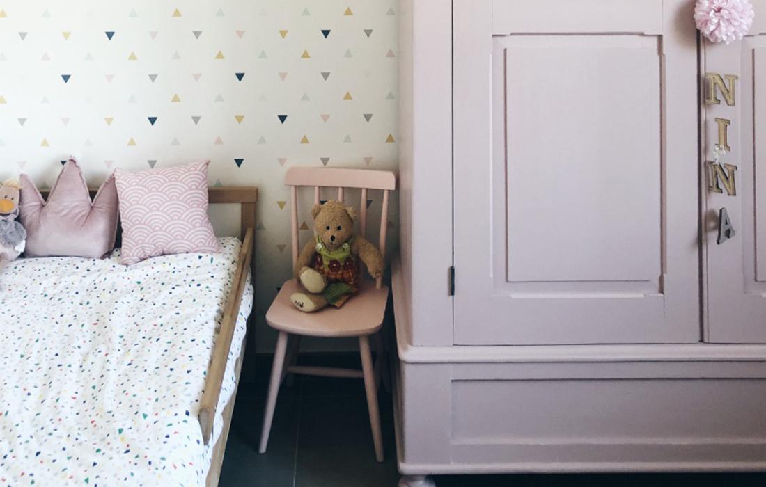 Letto da bambino basso in legno naturale con a fianco una seggiolina in legno rosa e armadio in legno rosa.