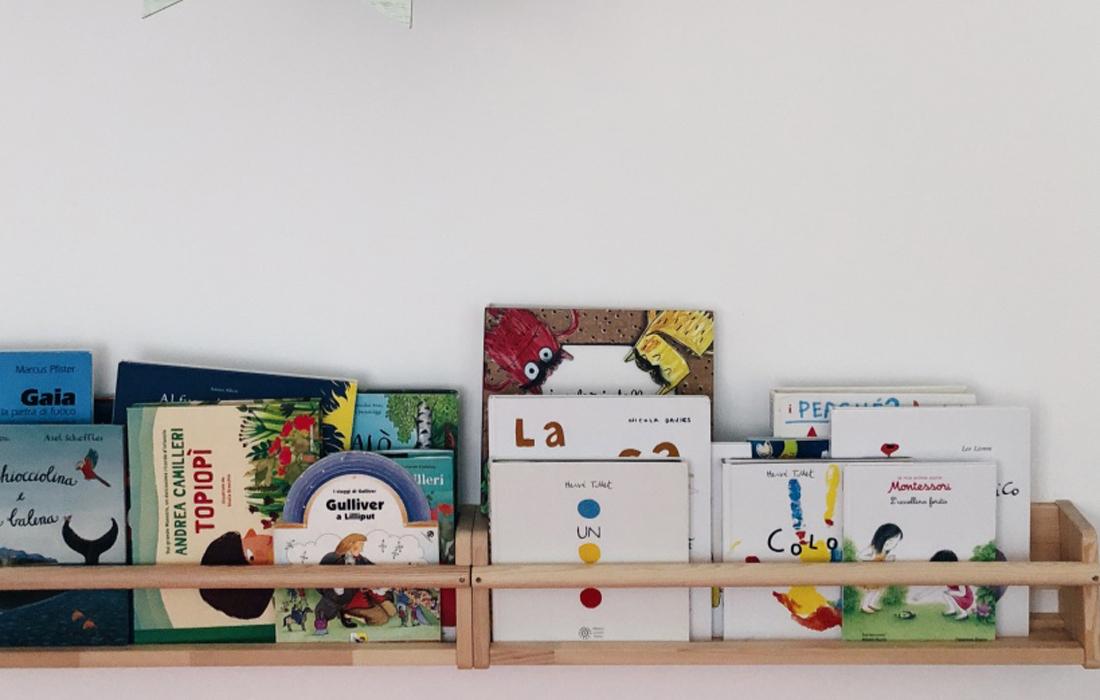 libreria frontale ikea in legno appesa al muro sulla quale sono riposti diversi libri da bambino.