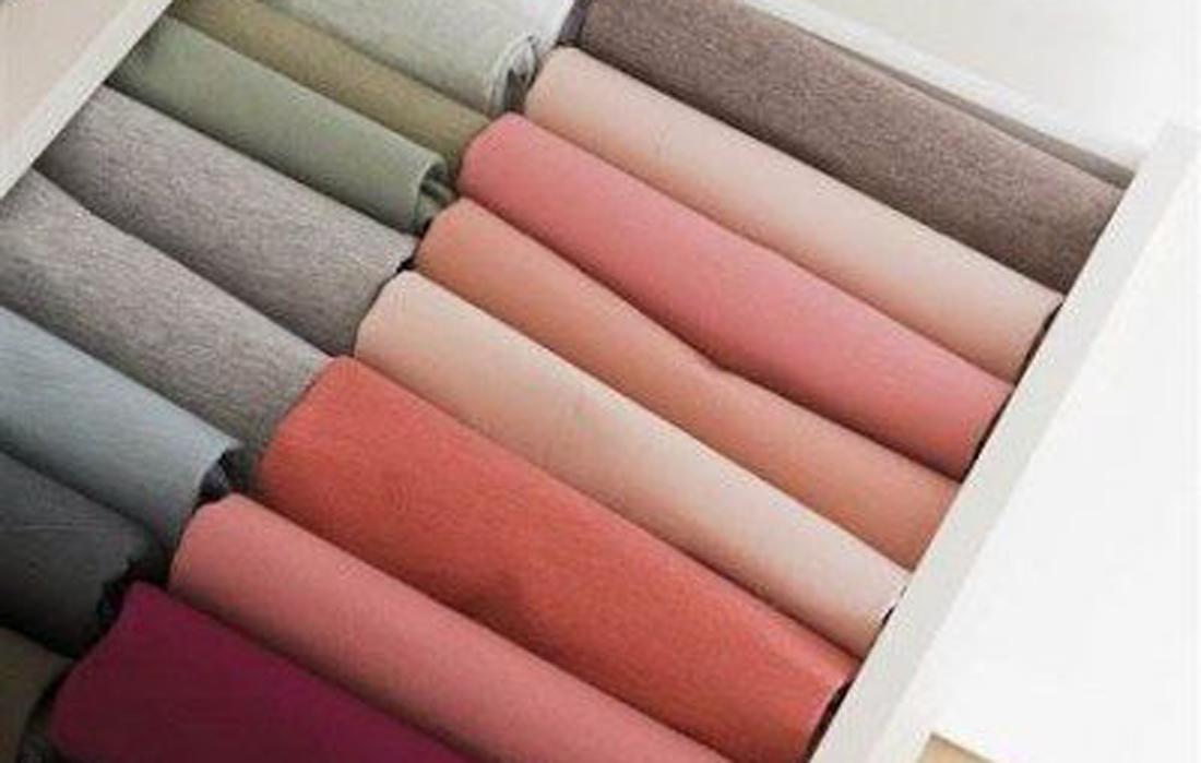cassetto aperto con t-shirt di diverso colore piegate in maniera ordinata