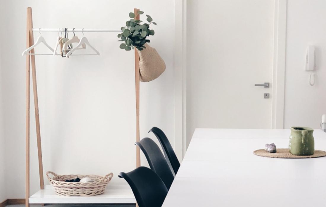 Tavolo bianco con sedie nere. Dietro un appendiabiti in legno e bianco con una cesta e dei fiori verdi