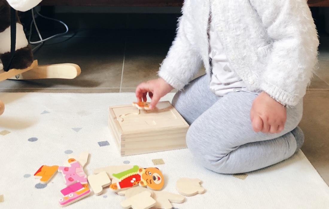 bambina i ginocchio riordina gioco in legno a incastro