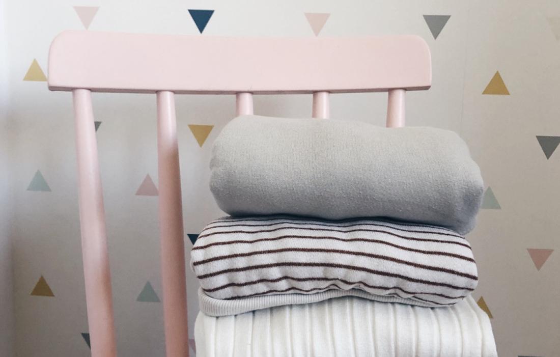 sedia in legno rosa chiaro con magliette impilate